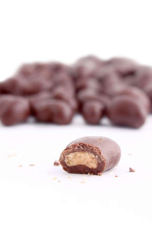 chocolaty: chocolate covered cashew nuts on a white background (not  isolated, short depth of field)