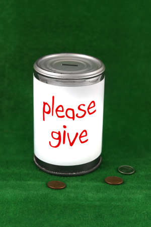 Change laying beside a donation charity tin can with the saying  please give