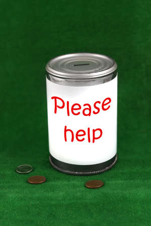 Change laying beside a donation charity tin can with the saying  please help