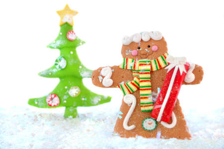 gingerbread man cookie in a winter wonderland wearing a scarf, holding a present  with christmas tree in the background photo
