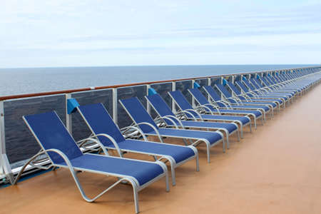 loungers: Long row of beach chair loungers on the deck of a ship with ocean in the background