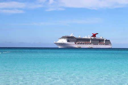 Cruise ship in the clear blue Caribbean ocean with boat tenders picking up passengers going to shore  Stock Photo