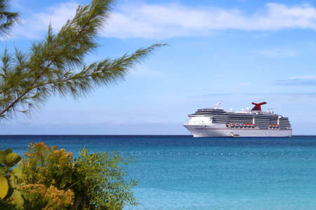 Cruise ship in the clear blue Caribbean ocean with greenery in the foreground Stock Photo