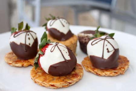 chocolate covered strawberries: Blanco y fresas cubiertas de chocolate oscuro en la torta trata de fantas�a y la placa blanca (poca profundidad de campo)