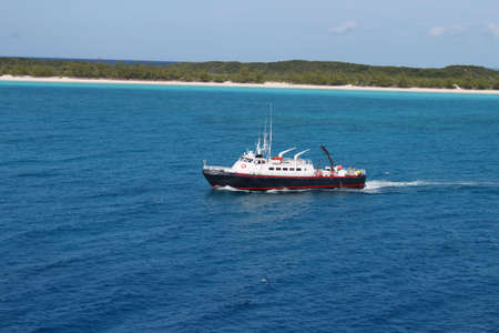View of beach at Half Moon Cay in the Bahamas with boat approaching  Stock Photo