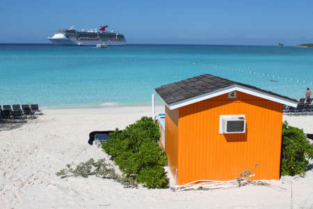Colorful tropical cabana or shelter on the beach of Half Moon Cay in the Bahamas with cruise ship in the background