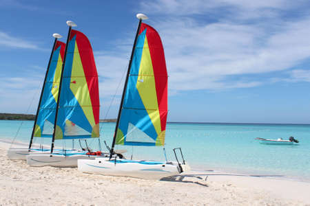 Colorful sailboats for rent on a tropical beach at Half Moon Cay in the Bahamas