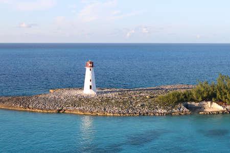 Lighthouse amongst turquoise blue sea at the entrance of the harbor in Nassau, Bahamas Stock Photo