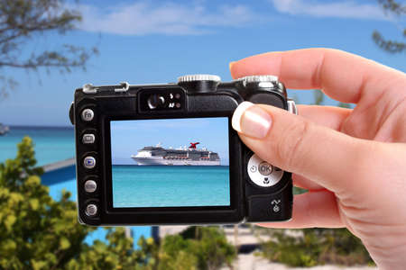 Woman taking picture of cruise ship in the clear blue Caribbean ocean with greenery in the foreground