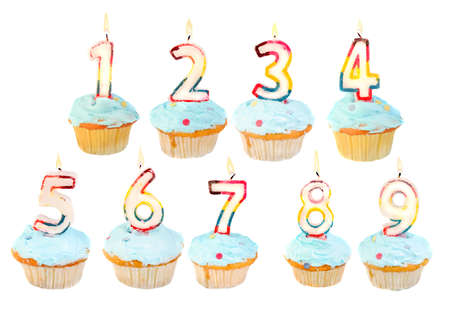 A set of birthday cupcakes with lit candles with numbers 1 to 9 스톡 콘텐츠