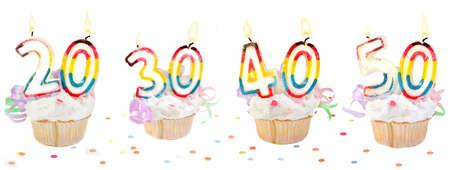 점등 된 촛불와 20, 30, 40, 50 같은 색종이와 기념 생일 컵 케이크