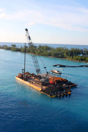 Barge in blue Caribbean water along the shore of Nassau harbor in the Bahamas