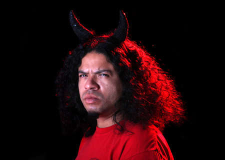 Angry man dressed as the devil with horns and  red creative lighting shining on his long curly black hair