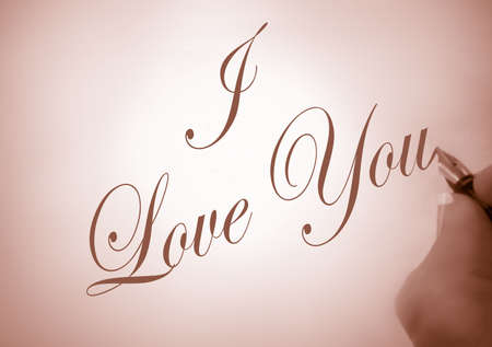 person writing: person writing I Love You in calligraphy in sepia tone Stock Photo