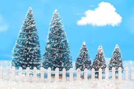 winter scene in colorful lilghts on  trees, bright  blue sky, and a white picket fence photo
