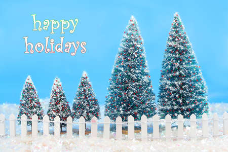 Christmas card saying happy holidays with a winter scene in colorful lilghts on trees, bright  blue sky, a white picket fence, and glittering snow photo