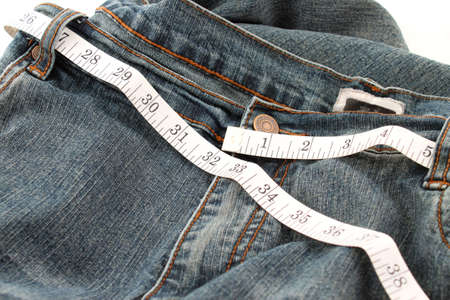 circumference: Measuring tape measuring 32 inches which is a healthy waist circumference for women. Stock Photo