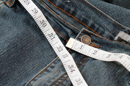 circumference: Measuring tape measuring 32 inches which is a healthy waist circumference for women.. Stock Photo