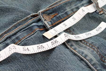 circumference: Measuring tape measuring an obese persons jeans waistline in inches Stock Photo