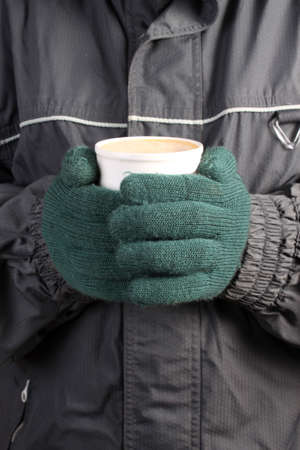 Person with green mittens, scarf and winter coat holding a warm beverage in a white cup on a cold  day