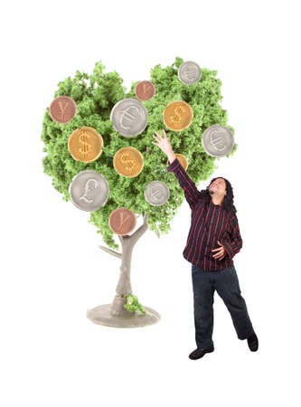 An ethnic looking man stretches to reach world currency coins growing from a tree on a white background Stok Fotoğraf