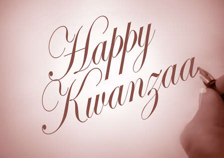 kwanzaa: Person writing Happy Kwanzaa in calligraphy with  sepia tone