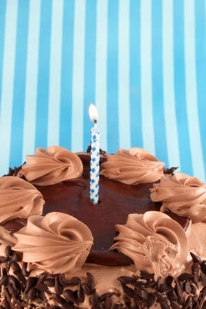 chocolaty: Black Forest Chocolate cake with lit birthday candle on a blue striped background Stock Photo