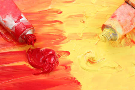 Red and yellow colors of artist's oil paints spilling out into a smudged painted background Stock Photo - 5990928