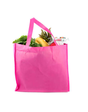 reusable: Colorful pink eco friendly grocery bags full of organic fruits and vegetable produce Stock Photo