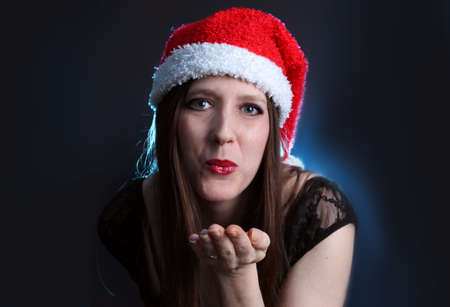 brunete: Pretty  woman with long brown hair dressed up in lace for christmas with red and white santa claus hat blowing you a kiss Stock Photo