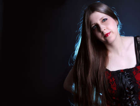 Pretty woman with really long shiny brown hair and red lipstick  on a black background with copy space