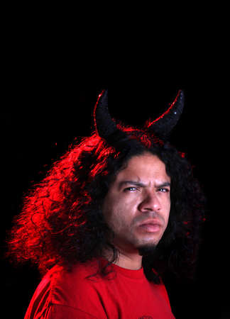 Angry man dressed as the devil with horns and  red creative lighting shining on his long curly black hair Banco de Imagens - 6073404