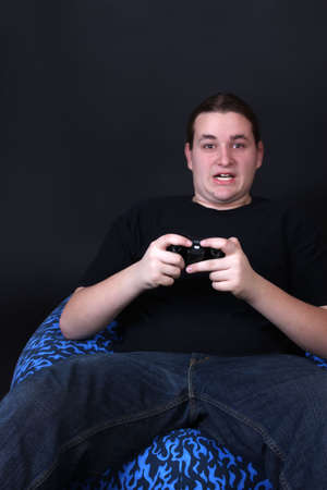 Teenager holding a video game controller with intense surprised expression on his face while sitting on a beanbag (shallow depth of field) photo