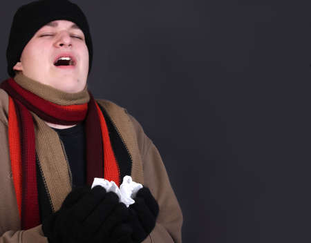 Teenage male sneezing into a tissue dealing with the winter flu, dressed in outerwear like gloves, scarf, and wool hat on a grey background