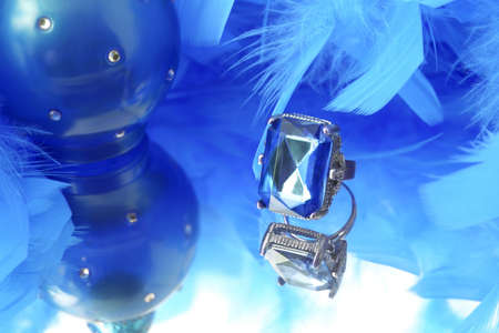 boas: glamorous diamond ring on vanity mirror with a blue  feather boa and perfume bottle in the background