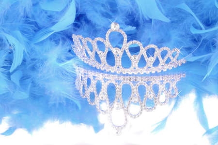 sparkling glamorous princess tiara with reflection and blue feathery boa in background Stock Photo