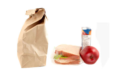 Paper bag for school lunch with a healthy, wholewheat sliced bread sandwich with vegetables, drink box, and an apple beside it