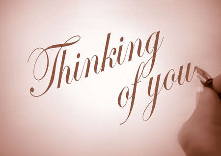 thinking of you: person writing thinking of you  in calligraphy in sepia tone