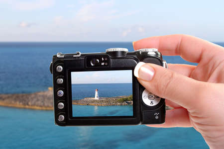 Woman taking a picture of a Lighthouse amongst turquoise blue sea at the entrance of the harbor in Nassau, Bahamas