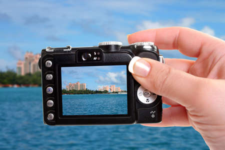 Woman takes a picture of famous hotels on Paradise Island in Nassau, Bahamas photo