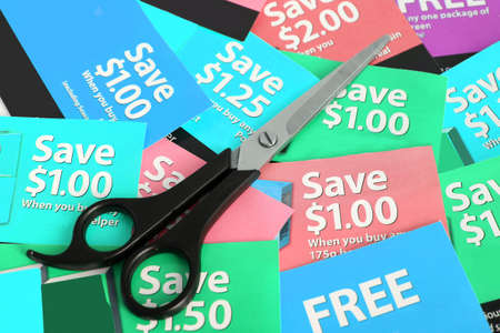 price cutting: Cutting coupons in different colors, and price ranges from free to a few dollars (short depth of field)