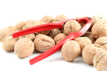 Whole walnuts in a pile with red nutcracker on a white background (NOT ISOLATED)