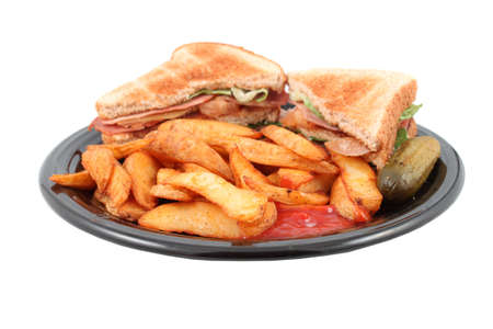 catsup: A plate of a bacon, lettuce and tomato sandwich also known as the BLT , french fried potato wedges, a pickle and catsup for dipping, isolated on a white background with short depth of field