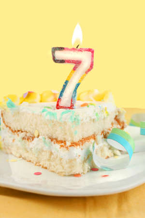 seventh: slice of seventh birthday cake with lit candle, confetti, and ribbon (shallow depth of field)