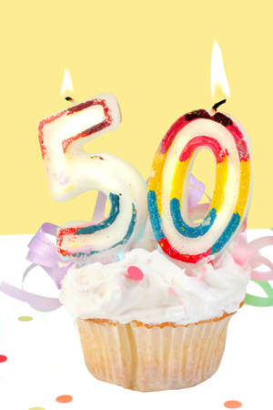 fiftieth birthday cupcake with white frosting and yellow decorative background  Stock Photo - 6142136