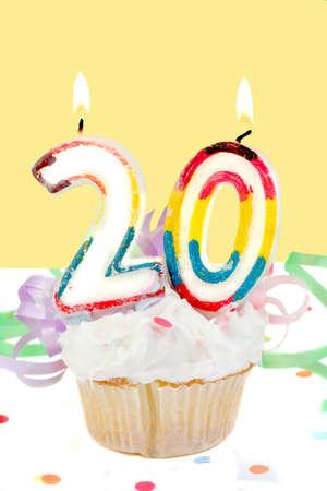 twentieth: twentieth birthday cupcake with white frosting and yellow decorative background  Stock Photo