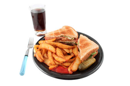 tomato catsup: A plate of a bacon, lettuce and tomato sandwich also known as the BLT , french fried potato wedges, a pickle and catsup for dipping with glass of cola