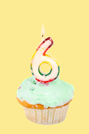 sixth birthday cupcake with green frosting on a yellow background photo