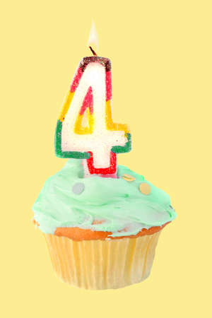 fourth birthday cupcake with green frosting on a yellow background photo