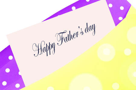 Happy Fathers day greeting card, note or letter in yellow and purple polkadot envelope photo